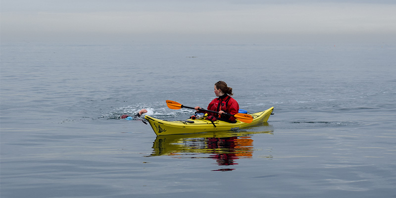 Swimmer accompanied by Safety kayak during Race Rocks Challenge 2019
