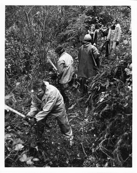 1974/75: A multicultural group of Pearson College UWC students encountering thick, west coast rainforest flora while blazing a hiking trail during a soggy Project Week experience.