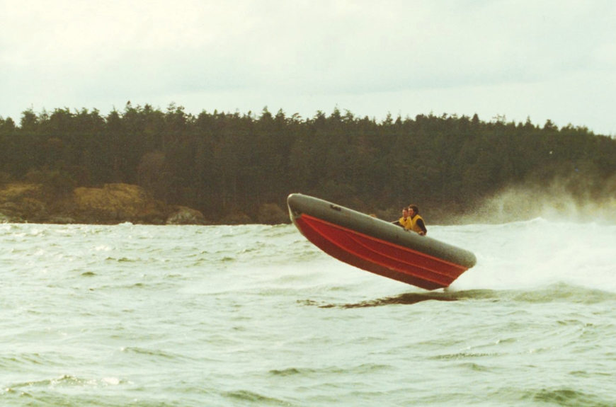 circa 1980-85:At sea in a rescue boat. Rigid-hulled Inflatable Boats (RIBs) are used today by life-saving crews around the world—but their roots are right here, on the shores of Pedder Bay at Pearson College. Well, almost. The first RIB was constructed by students at UWC Atlantic in Wales, Pearson's sister college, in the mid '60s, using plywood glued to the frame of a dinghy-type rescue boat. In 1974 (and several prototypes later), drawings and materials for two RIBs were sent to Pearson College, then in its inaugural year. That summer the College loaned one of the boats to the Canadian Coast Guard. It was fast, solid, economical—and took off as a rescue boat around the world. Today, RIBs are widely used as rescue, whale-watching and dive boats.
